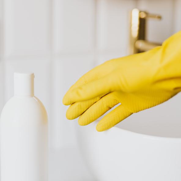 Une personne s'apprête à laver le robinet avec un gant et un produit d'entretien